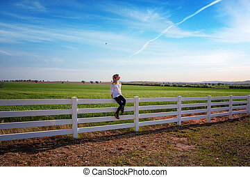 Woman sitting on white farm fence in rural fields