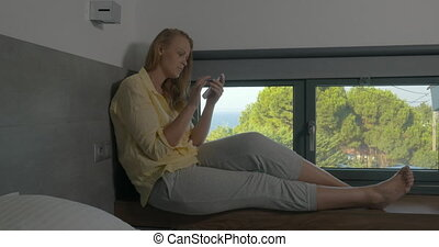 Woman sitting on window-sill and using phone