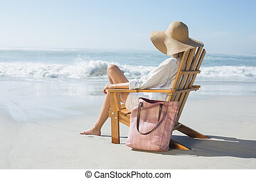 Woman sitting on wooden deck chair