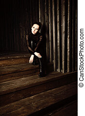 Woman sitting on wooden stairs