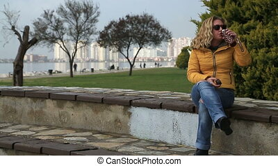 Woman sitting outdoor and drinking