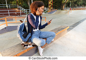 Woman sitting outdoors in park using mobile phone listening music with earphones.
