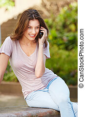 Woman sitting outdoors talking on mobile phone