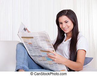 Woman sitting reading a newspaper
