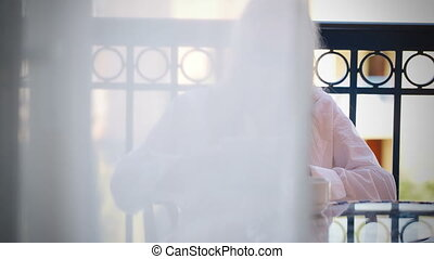 Woman sitting reading a tablet-pc on a balcony - Dolly shot...