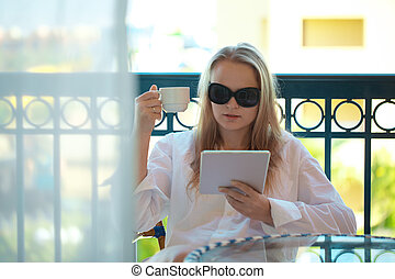 Woman sitting reading a tablet-pc on balcony