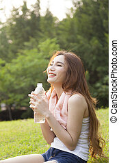 Woman sitting rest after exercise. Hand holding a bottle of ...