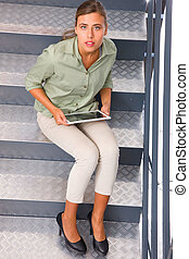 Woman sitting staircase with digital tablet