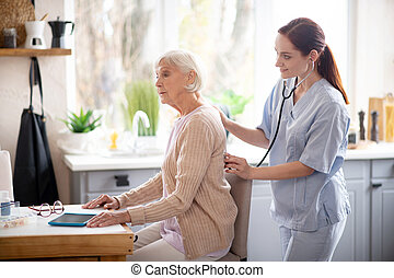 Retired woman sitting still while nurse examining her