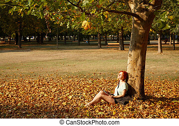 woman sitting under a tree in park