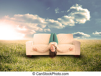 Woman sitting upside down on couch in field