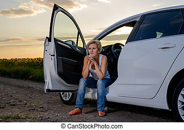 Woman sitting waiting for roadside assistance in the open door of her car parked on a rural road at sunset staring glumly ahead