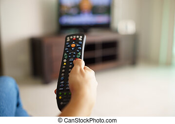 Woman sitting watching tv changing channel with remote -...