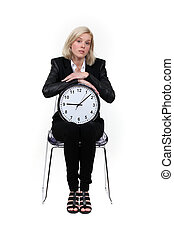Woman sitting with a clock on her knees