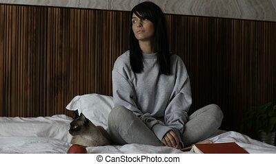 Woman sitting with cat on bed