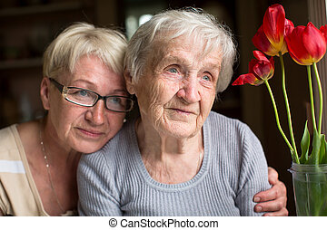 Woman sitting with her elderly moth
