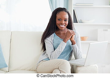 Woman sitting with her laptop on sofa