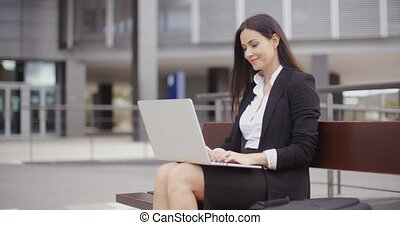 Woman sitting with laptop on bench outdoors