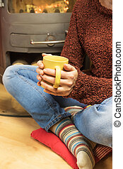 Woman sitting with tea mug in front of burning stoves.