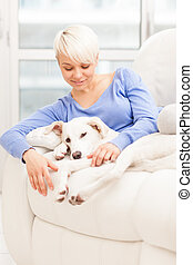 Woman sitting with young dog on the sofa