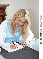Woman sitting writing at home