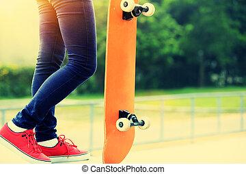 woman skateboarder legs at skatepark