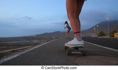 Woman skateboarder rides on a Board on the slope against the sky from the mountain