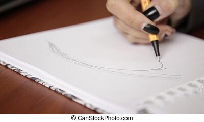 woman sketching on a notebook, drawing eye with pencil in sketchbook