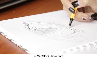 woman sketching on a notebook, drawing eye with pencil in...