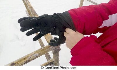 woman skier puts on winter gloves - woman skier puts on...