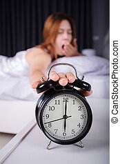 woman sleeping and wake up to turn off the alarm clock in morning