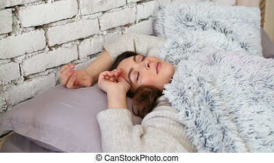 Woman sleeping and waking up in bed in the morning. lazy...