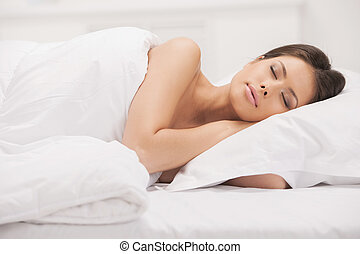 Woman sleeping. Beautiful young woman lying on the sofa and keeping eyes closed