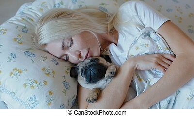 Woman sleeping in bed embracing puppy pug. - Young woman...