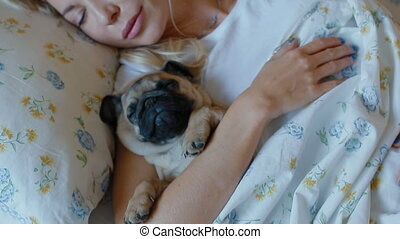 Woman sleeping in bed with puppy pug