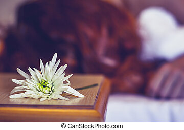 Woman sleeping in hotel room with flower next to her face