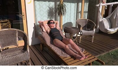 Woman sleeping in the lounge chair near bungalow