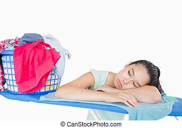 Woman sleeping on an ironing board