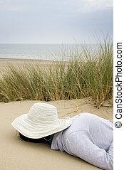 woman sleeping on beach