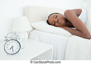 Woman sleeping while her alarm clock is ringing