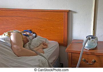 This middle aged Caucasian woman is sleeping with a CPAP machine on the bedside table while the mask is on her face, treating sleep apnea.