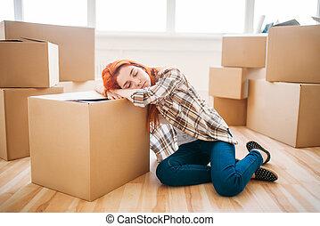 Woman sleeps on carton box, moving to new house