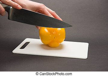 Woman slices a yellow bell pepper