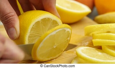Woman slices the citrus fruit on a wooden cutting board with...