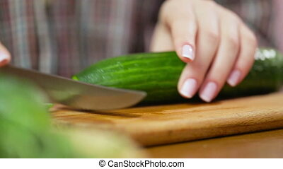 Woman slicing cucumber. Female hands cut green cucumber rings. Big knife. In the kitchen. Wooden board. house-proud woman. Fresh cucumber. Fresh vegetables. sharp knife.