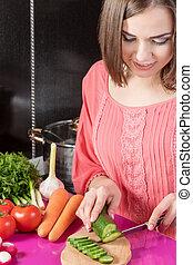 Woman slicing cucumber