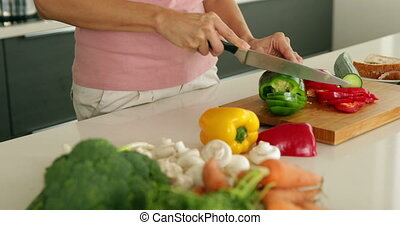 Woman slicing green pepper and smiling at camera at home in...
