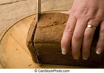 woman slicing loaf of rye bread