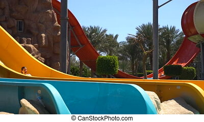 Woman sliding on water slide in water park in slowmotion