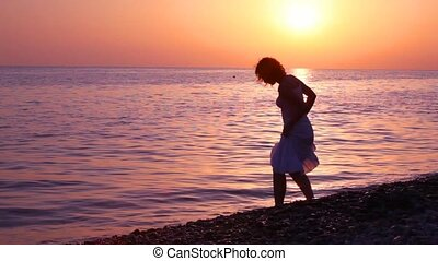 woman sloshing water in sea, sunset sky in background